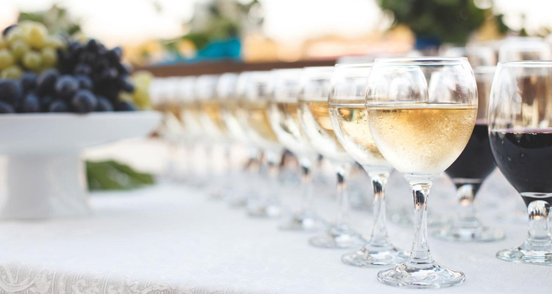 Weingläser gefüllt mit rotem und weißem auf einer weiß gedeckten Tafel.