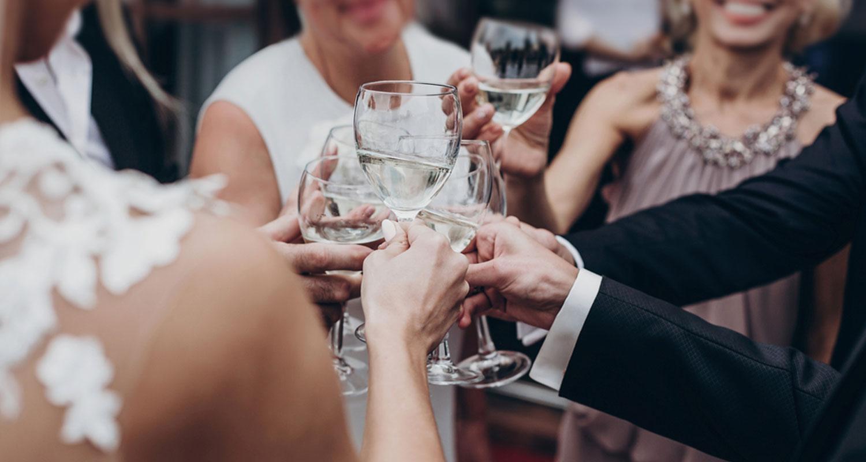 Auf einer Hochzeit stoßen Freunde mit Wein an.