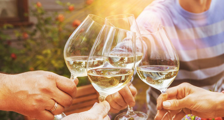 Freunde stoßen mit Weißwein an auf die Weißwein-Saison an